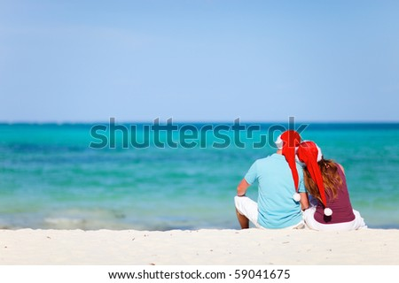 Back view of young romantic couple in red Santa hats sitting on tropical white sand beach
