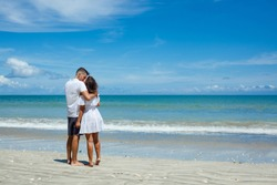 Back view of young romantic couple in white clothes standing on tropical beach. Man and woman huging on right side of photo. Blue sky and see on background
