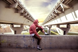 back view of young sitting sportsman in sweatshirt under the bridge architecture , urban colorful landscape, beautiful cityscape with young guy in hoodie