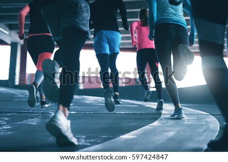Back view of young sportspeople running on race track at sports ground.  #597424847