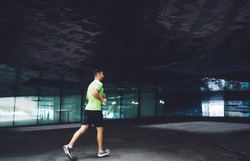 Back view of young sporty male runner in activewear and sneakers jogging along dark empty hall of modern building during training in city