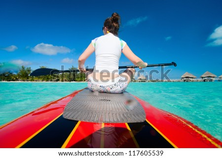 Back view of young sporty woman on paddle board