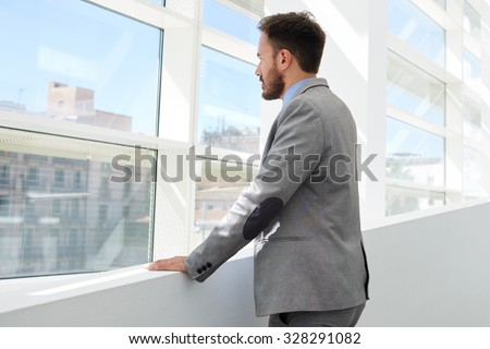 Back view of young successful businessman thinking about something while looking in big office window, confident serious men managing director dressed in formal wear enjoying calm after hard work day