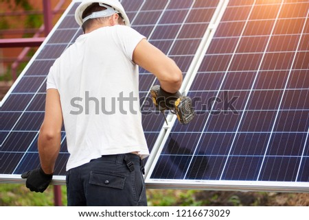 Back view of young technician connecting solar photo voltaic panel to metal platform using electrical screwdriver on bright sunny summer day outdoors. Alternative renewable energy generation concept.