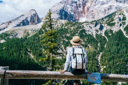 Back view of young tourist with paper map sitting on wooden fence and admiring mountain range and forest during trip to Karersee Lake