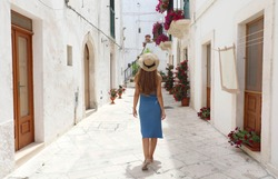 Back view of young tourist woman on ancient street in old town. Travel woman in straw hat and blue dress enjoying vacation in Europe. Tourism and travel concept.