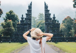 Back view of young tourist women enjoy her holiday in Bali with the view of traditional Hindu gate in Bali island, Indonesia.