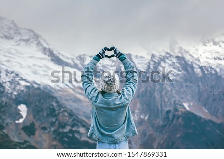 Back view of young traveler girl in gloves and hat standing over snowy mountain peaks and making shape of love heart by hands. Winter travelling scene, wanderlust concept. ストックフォト ©