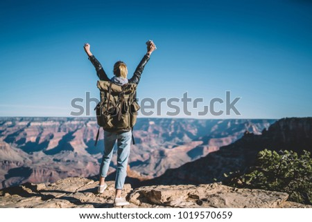 Back view of young wanderlust feeling victory conquering mountain in Grand Canyon, female traveler with backpack raising hands enjoying beautiful nature from high rocky hills getting to destination