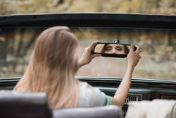 back view of young woman adjusting rearview mirror in cabriolet on blurred foreground