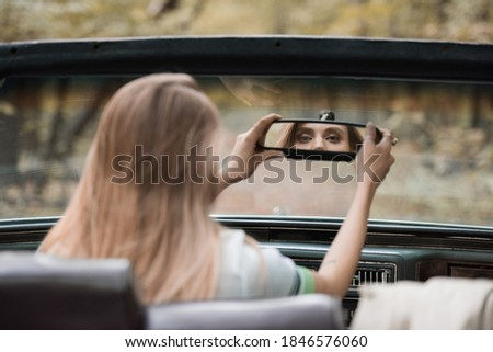 back view of young woman adjusting rearview mirror in cabriolet on blurred foreground Foto stock ©
