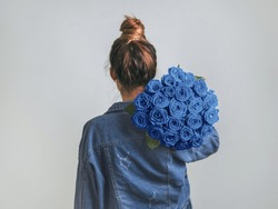 Back view of young woman in denim jacket holding bunch of blue roses on shoulder. Girl with bun updo in jeans holding flowers in classic blue color of year 2020. Copy space.