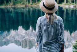 Back view of young woman in hat and striped shirt standing on shore of tranquil Karersee Lake with reflection of mountain ridge on sunny day in nature