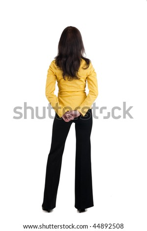 Back view of young woman in yellow suit looking at wall. The rear view. Isolated over white background.