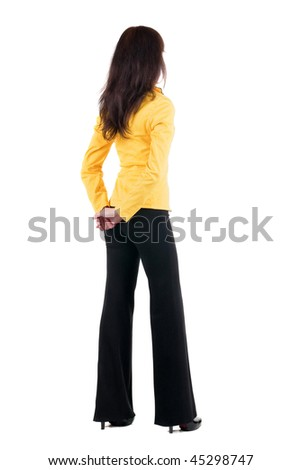 Back view of young woman in yellow suit looking at wall. The rear view. Isolated over whute background
