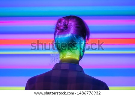 Back view of young woman looking around at modern immersive exhibition or club event with changing multi color projector light illumination. Digital art, technology and entertainment concept