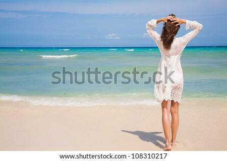 Back view of young woman looking at ocean