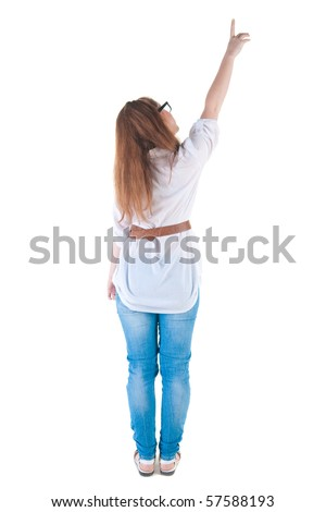 Back view of young woman points at wall. The rear view. Isolated over white background