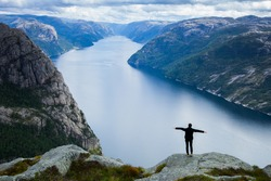 Back view of young woman relaxing in Norway mountains. Travel concept. Girl Traveler. Travel Destination Concept. Wanderlust Traveler Lifestyle Nature Trip Concept