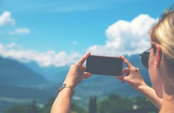 Back view of young woman using smartphone camera for making picture of Swiss Alps. Female traveler blogger taking photos on mobile phone during summer journey vacations.