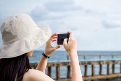 Back view of young woman wearing a hat taking photo with her smart phone on landscape view
