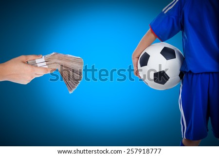 Back view of youth soccer player in blue uniform and little kid holding a ball and hand holding stacks of banknotes on blue background, Concept of achievements in business for soccer