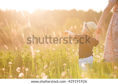 Back view on a cute little toddler boy in a straw hat holding his mother\'s hand and pointing into distance. Adorable child walking with his mom in the park on a sunny summer day. Family on sunset