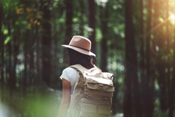 Back view on traveler backpack and hipster girl wearing hat. Young brave woman traveling alone among trees in forest on outdoors. Lens flare effect