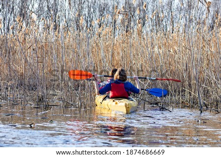 Back view on two woman padle in yellow kayak on lake among bulrush at autumn season Stock fotó ©