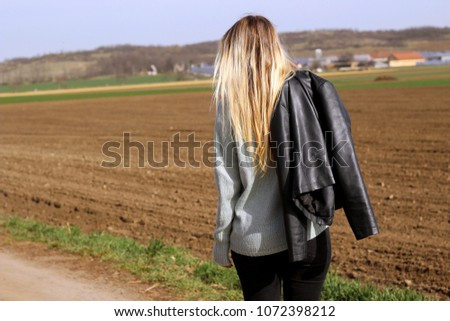 Back view on young blond woman walking on field . Wearing knitted sweater and jeans, in his hand he has a black leather jacket. Girl outdoors. Lifestyle. Space for text.