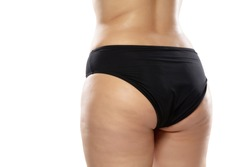 Back view. Overweight woman with fat cellulite legs and buttocks, obesity female body in black underwear isolated on white background. Orange peel skin, liposuction, healthcare and beauty treatment.