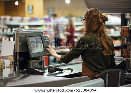 Back view photo of cashier woman on workspace in supermarket shop. Looking aside. #623084894