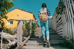 back view photo of young beauty woman backpacker walking on wooden walkway stairs preparing going to travel hotel check in during summer vacation holiday.