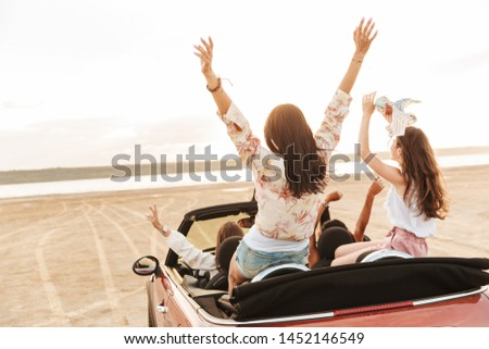 Back view picture of a beautiful pretty young pretty women friends driving the car.