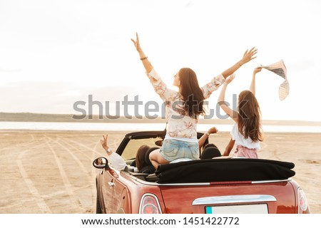 Back view picture of a beautiful pretty young pretty women friends driving the car raised up their hands.