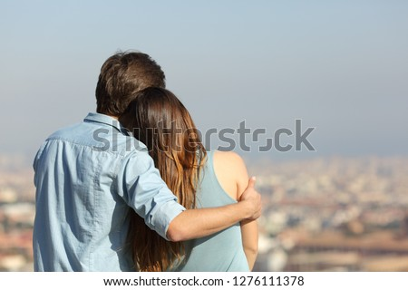 Back view portrait of a happy couple dating contemplating the city