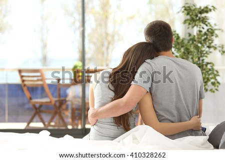 Back view portrait of a happy couple sitting on the bed looking the balcony outdoors through a window of the bedroom of a house