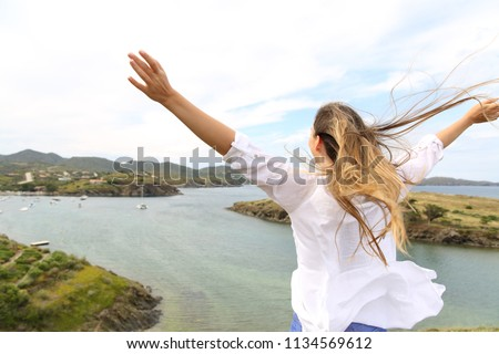 Back view portrait of a happy woman raising arms to the wind