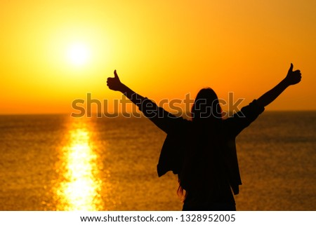 Back view portrait of a happy woman silhouette gesturing thumbs up outstrestching arms celebrating success at sunrise