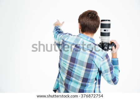 Back view portrait of a male photographer holding photo camera and pointing on something isolated on a white background #376872754