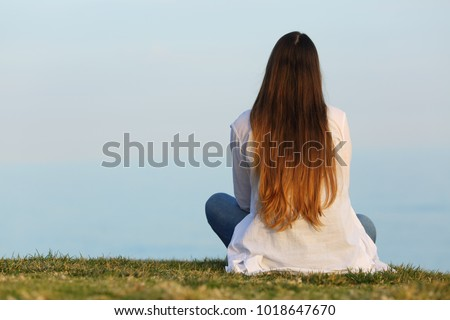 Back view portrait of a woman alone watching the sky sitting on the grass
