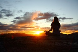 Back view portrait of a woman silhouette doing yoga at sunset in the mountain