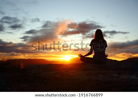 Back view portrait of a woman silhouette doing yoga at sunset in the mountain Foto stock ©