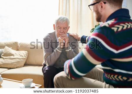 Back view portrait of male psychologist consoling depressed senior man during therapy session, copy space