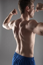 Back view portrait of shirtless attractive guy flexing his muscles and showing biceps. Isolated on blue-gray background