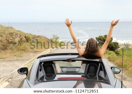 Back view portrait of two happy tourists driving a convertible car on vacation #1124712851