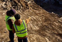 Back view portrait of two industrial workers wearing reflective jackets, one of them African, standing on cliff overlooking mineral mines on worksite, copy space