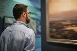 Back view portrait of young bearded man looking at pictures in modern art gallery or museum, copy space