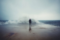 Back view portrait of young man standing against the sea on a large concrete pier with big wave beating with splash in a cloudy storm weather, feeling of freedom, male person enjoying rainy day alone