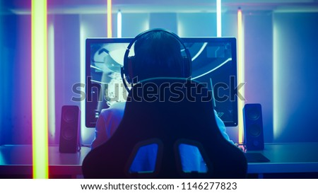 Back View Shot of the Professional Gamer Playing in First-Person Shooter Online Video Game on His Personal Computer. Room Lit by Neon Lights in Retro Arcade Style. Online Cyber e-Sport Internet. #1146277823